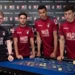 A smiling Eddie Howe with AFC Bournemouth players who don't look too happy having a gaming business as their official shirt sponsor.