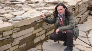 Neil Oliver with the foundations of A stone age temple on Orkney