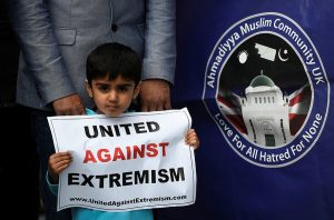 Ahmadi boy holds a poster in a vigil which directs to the Ahmadiyya website, next to their main slogan of 'Love for All, Hatred for None'