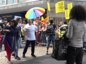 Andrew Moffat (holding the 6-colour 'diversity' rainbow umbrella) leading the Birmingham Gay Pride parade last month.
